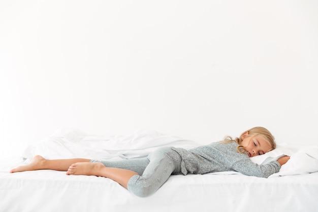Ritratto integrale della ragazza pacifica addormentata in pigiami grigi che si trovano a letto