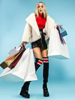 Ritratto integrale di bella donna sorridente che cammina con i sacchetti della spesa variopinti isolati sopra fondo blu