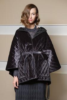 Ritratto integrale di bella ragazza in cappotto e poncho cappotto.