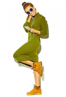 Ritratto integrale di bella ragazza sorridente felice sveglia della donna del brunette in vestiti casuali verdi di estate dei pantaloni a vita bassa isolati su musica d'ascolto bianca in smartphone con le cuffie