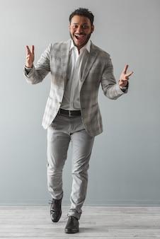 Ritratto integrale di elegante ragazzo afro in abito grigio.