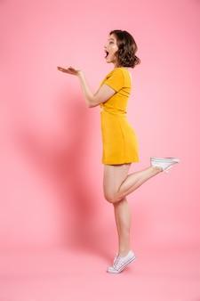 Ritratto integrale di giocosa donna attraente in abito giallo in piedi su una gamba sola, mostrando il palmo vuoto