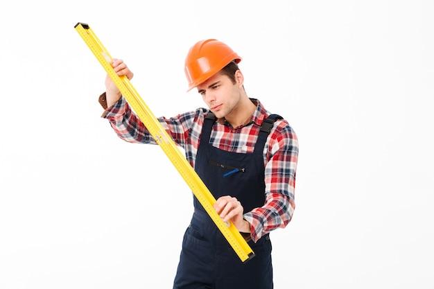 Ritratto integrale di giovane costruttore maschio concentrato