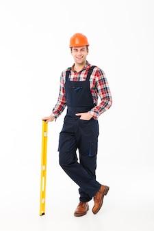 Ritratto integrale di giovane costruttore maschio sorridente