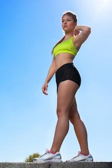 Ritratto integrale di giovane donna caucasica nell'usura di forma fisica all'aperto