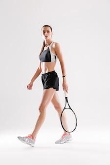Ritratto integrale di giovane donna focalizzata in abbigliamento sportivo