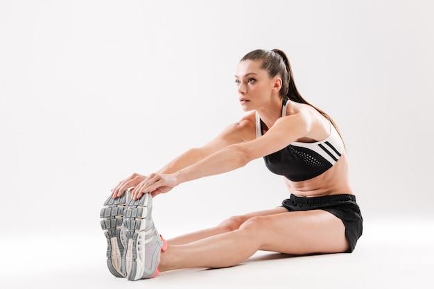 Ritratto integrale di giovane sportiva che allunga i muscoli