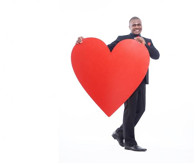 Ritratto integrale di giovane uomo africano che tiene grande cuore rosso