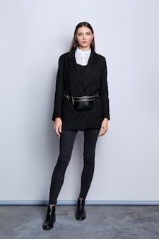 Ritratto integrale di ragazza alla moda in giacca nera, jeans, camicia bianca e marsupio