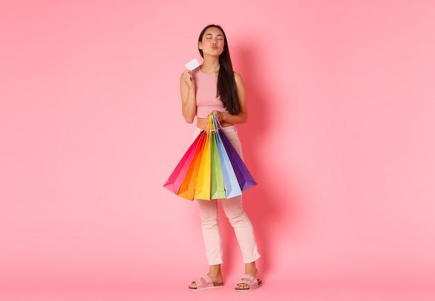 Ritratto integrale di ragazza asiatica glamour sciocca e carina che ama sprecare soldi nei negozi, fare il broncio e fare il bacio, esprimere amore per la sua carta di credito e conto in banca, tenendo le borse della spesa.