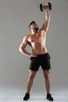 Ritratto integrale di un bodybuilder maschio senza camicia forte sano