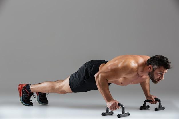 Ritratto integrale di un forte culturista maschio senza camicia muscolare