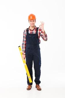 Ritratto integrale di un giovane costruttore maschio allegro