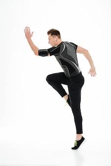 Ritratto integrale di un giovane sportivo concentrato nei salti delle cuffie