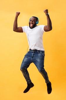 Ritratto integrale di un giovane uomo afroamericano della ciliegia che ascolta la musica con le cuffie