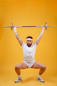 Ritratto integrale di un uomo di forma fisica che accovaccia con il bilanciere