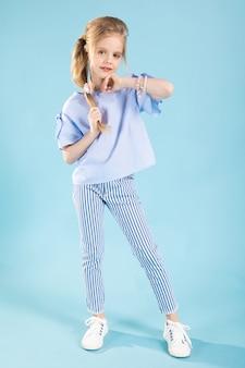 Ritratto integrale di una bella ragazza in abiti blu su un blu.