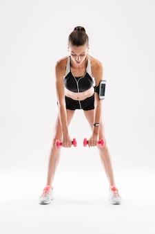 Ritratto integrale di una donna motivata di forma fisica in abiti sportivi