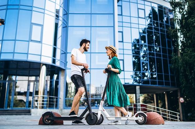 Ritratto integrale di una giovane coppia romantica con scooter elettrici, camminando in città.