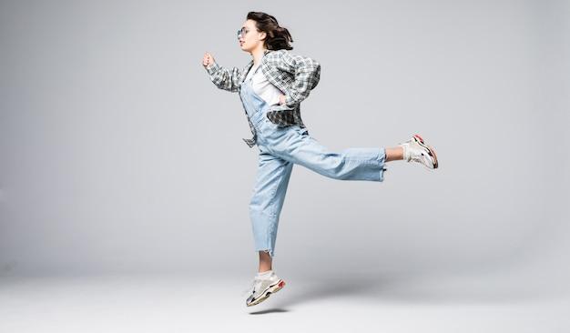 Ritratto integrale di una giovane donna allegra che salta e che celebra