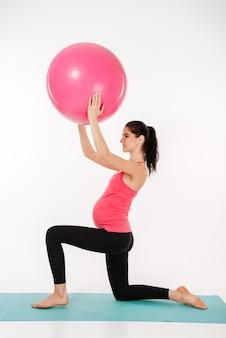 Ritratto integrale di una giovane donna incinta che fa le esercitazioni