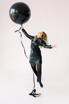 Ritratto integrale di una ragazza allegra in vestito nero che tiene grande mongolfiera mentre saltando e volando, esaminando macchina fotografica isolata sopra fondo bianco