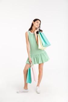 Ritratto integrale di una ragazza graziosa nella conversazione del vestito