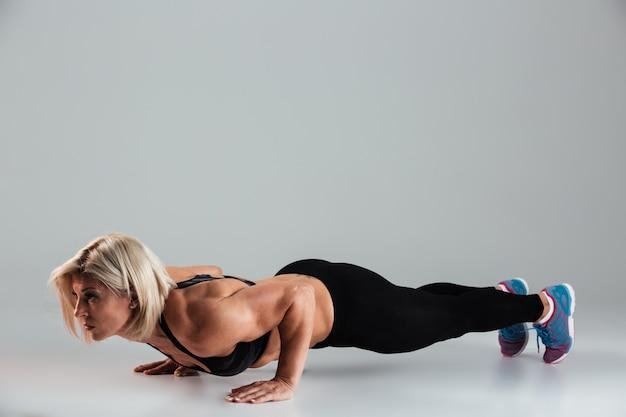 Ritratto integrale di una sportiva adulta muscolare in forma