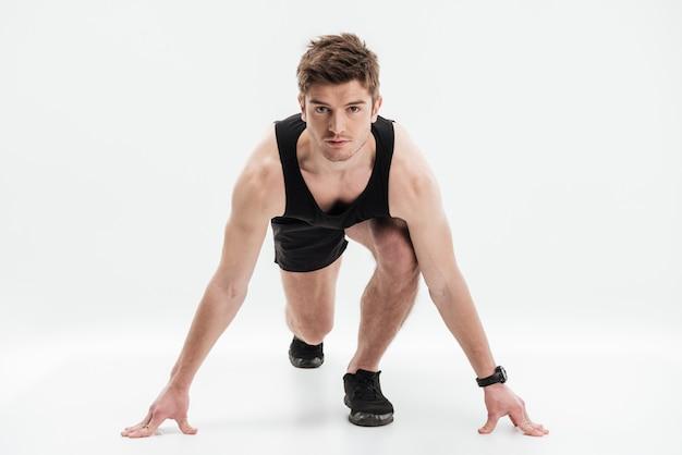 Ritratto integrale di uno sportivo concentrato pronto a correre