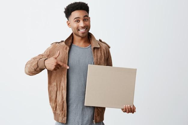 Ritratto isolato di giovane uomo dalla pelle nera con acconciatura afro in look casual alla moda tenendo il cartone, indicandolo con la mano, guardando a porte chiuse con espressione eccitata