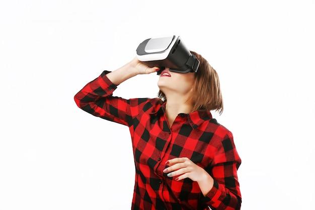 Ritratto isolato di una donna con capelli rossi usando una cuffia avricolare di realtà virtuale.