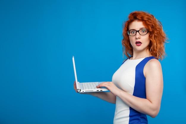Ritratto isolato di una ragazza di affari che tiene un computer portatile. la ragazza sembra sorpresa e confusa. affari ed emotivo