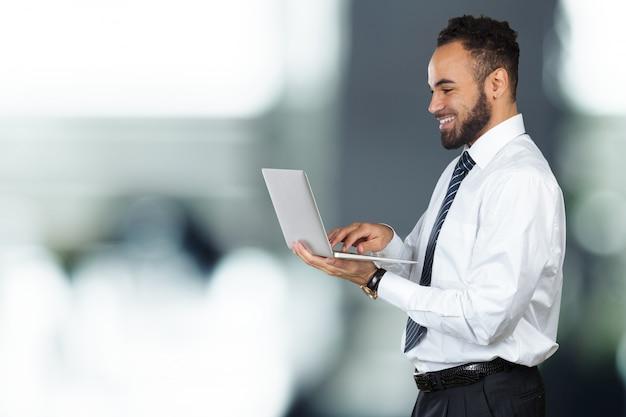 Ritratto isolato giovane computer portatile maschio nero della tenuta