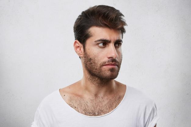 Ritratto laterale del forte maschio con la barba e l'acconciatura alla moda che indossa la maglietta bianca che osserva da parte accigliato il suo viso con sguardo pensieroso pensando al suo lavoro