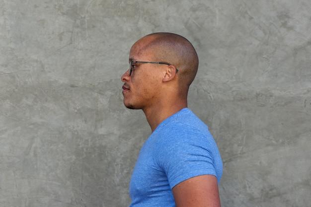 Ritratto laterale dell'uomo africano serio con gli occhiali