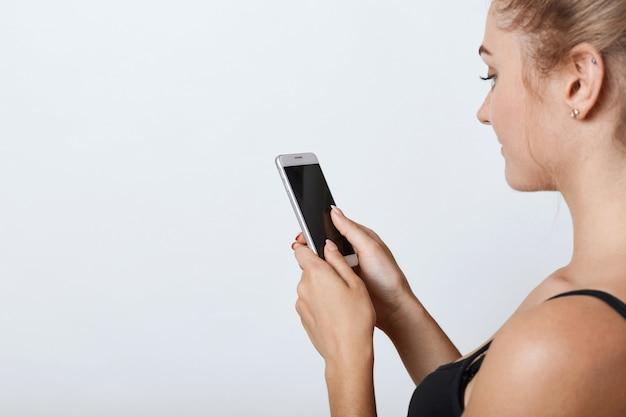 Ritratto laterale della femmina con pelle pura sana tenendo il telefono cellulare in mano con schermo vuoto, leggendo le notizie online mentre si utilizza la connessione internet gratuita. persone, tecnologie moderne, comunicazione