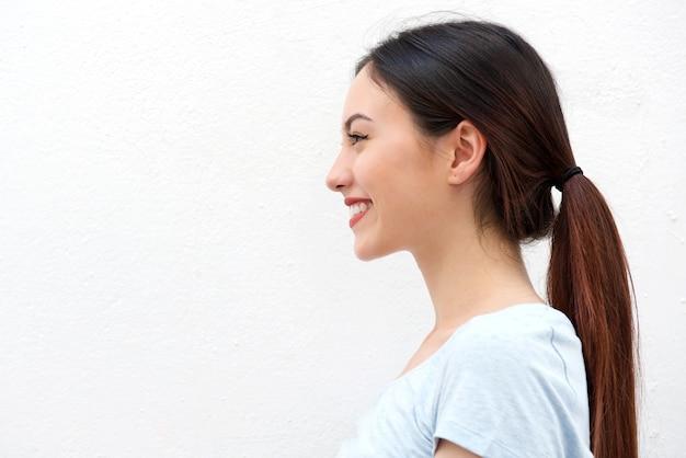Ritratto laterale della giovane donna in buona salute con sorridere lungo dei capelli
