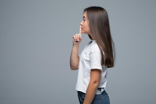 Ritratto laterale di bella donna asiatica che sorride e che mostra le mani del segno per zitto su fondo grigio