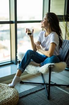 Ritratto laterale di una donna sorridente che si rilassa a casa con la tazza di tè