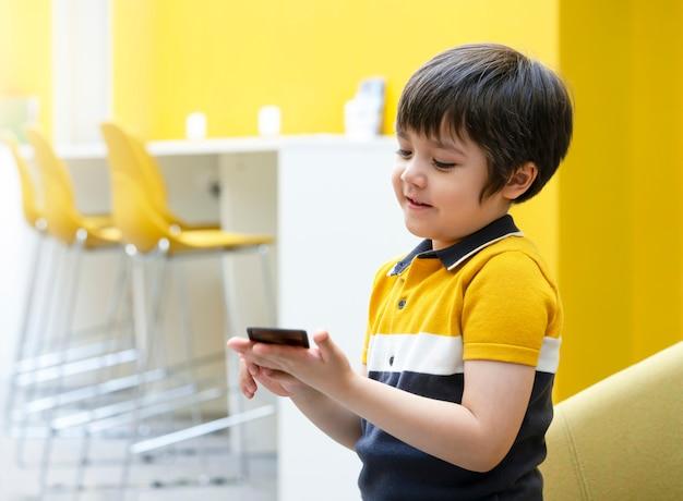 Ritratto laterale di vista del bambino attivo con il gioco di carte sorridente della tenuta della faccia, ragazzo del bambino che gioca la carta di addestramento nell'aula alla scuola, concetto di sviluppo e di istruzione