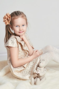 Ritratto little girlbeautiful vestito e bambola giocattolo