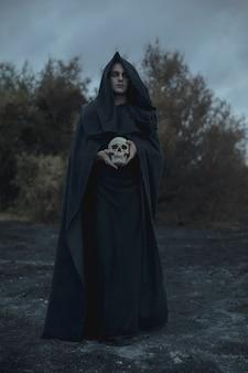 Ritratto lungo di un uomo vestito da mago oscuro con teschio