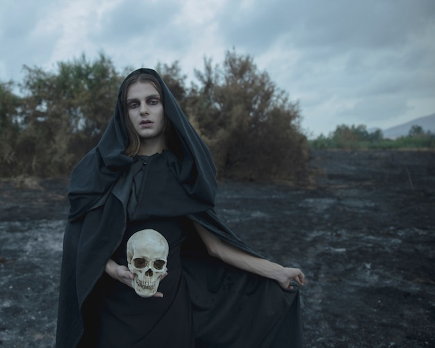 Ritratto lungo di un uomo vestito da strega oscura con teschio