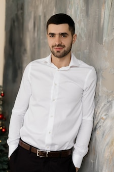 Ritratto maschile l'uomo castana bello in camicia bianca e jeans neri di classe posa in studio grigio
