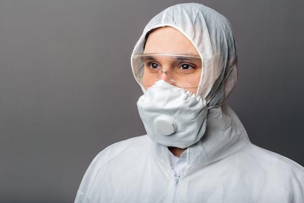 Ritratto medico caucasico in tuta medica protettiva, rischio biologico, maschera medica ffp3, occhiali. dottore in abbigliamento di protezione chimica per la disinfezione di coronavirus covid-19.