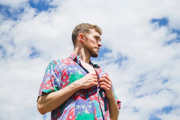 Ritratto medio basso del colpo dell'uomo alla moda che osserva via