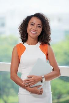 Ritratto medio della donna di affari che sta con il computer portatile alla finestra dell'ufficio