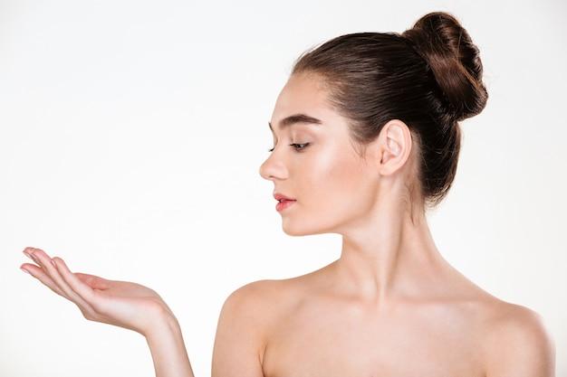 Ritratto nel profilo di bella giovane donna che ha pelle fresca che posa mostrando prodotto sul suo spazio della copia della palma