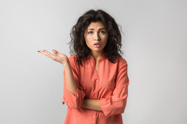 Ritratto o giovane donna graziosa, razza mista, capelli ricci, stressato, emozione frustrata sul viso, pensando al problema, isolato, camicetta arancione,