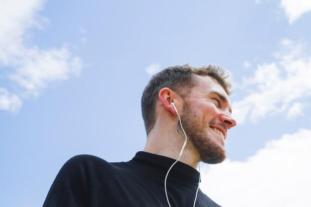 Ritratto obliquo di un uomo di smiley che osserva via